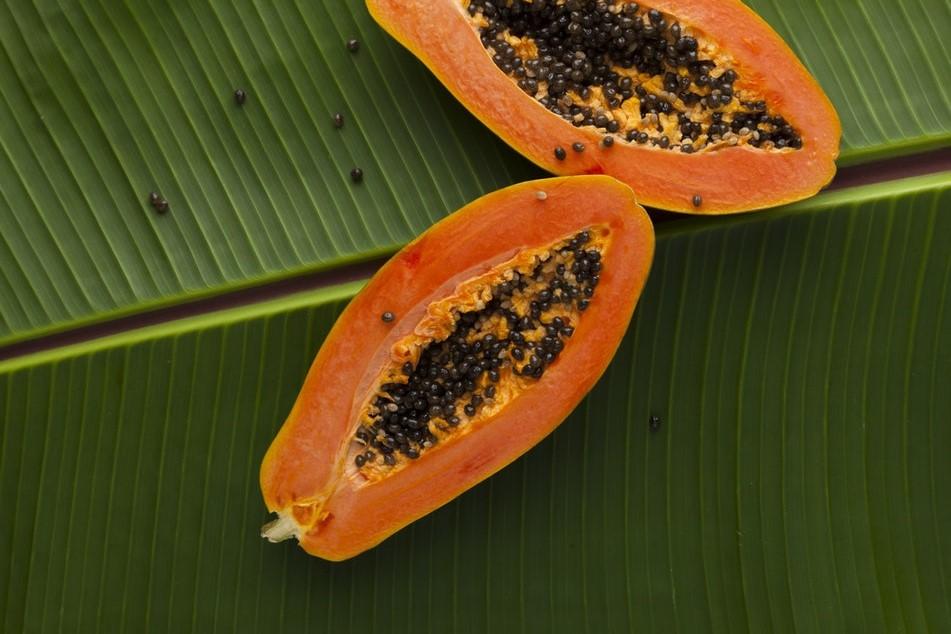 Papaye coupée en deux sur une feuille de palmier